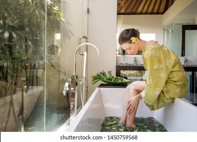 Young woman takes a bath in the herbal tub, a woman in a green bathrobe sitting on the tub, spa weekend, wellbeing, body care and beauty concept