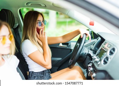Young woman takes control of a car while the driver using mobile phone and losing concentration.