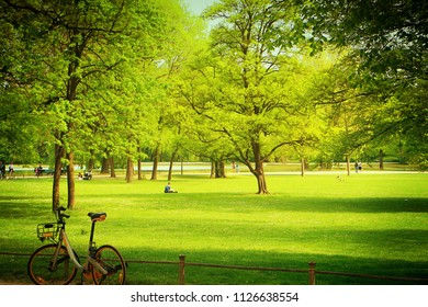 Young woman takes a moment relax to  read leisurely at Englischer Garten, green oasis in the middle of Munich