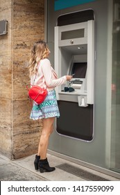 Young woman takes money from an ATM. Finance, credit card, withdrawal of money. Grabs a card from the ATM