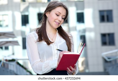 Young woman takes notes in his diary. Woman office worker writes new information daily. Office employee on the background of the business center. Keep a record for the client.