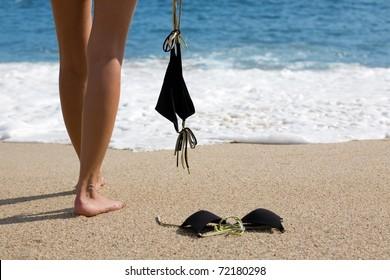 Young woman takes off bikini to swiming in the sea.
