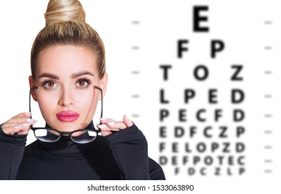 Young woman takes off glasses and eye chart become blurred. Ophthalmologist consultation.