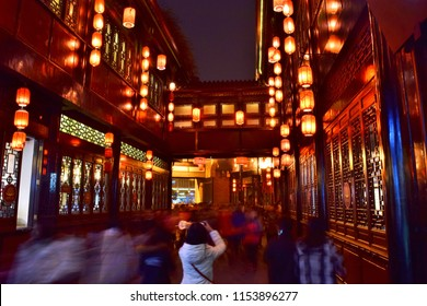 Young Woman Takes a Photo of Chinese Lanterns Hanging from Old Traditional Buildings Along Chengdu's Famous Jinli Street at Night - Chengdu, China (Summer)