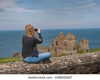 Young woman takes photos of Dunluce Castle in North Ireland - travel photography