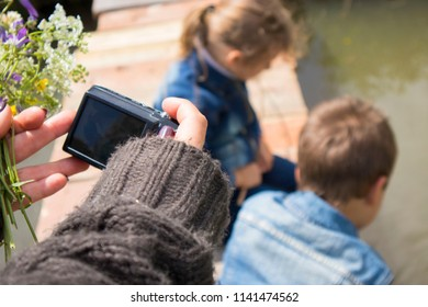 young woman takes pictures of children on the river bridge on a summer day . girl photographer with retro camera