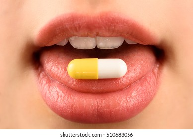 Young woman takes a pill
