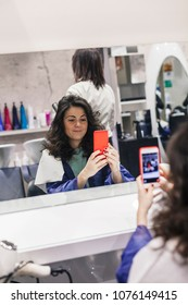 Young woman takes selfie with her smartphone in front the mirror of a hairdresser's shop after cutting and styling