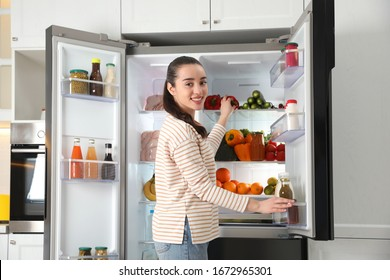 Young woman taking bell pepper out of refrigerator in kitchen