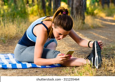 Young woman taking a break and checking calories on her smart phone after workout in the forest