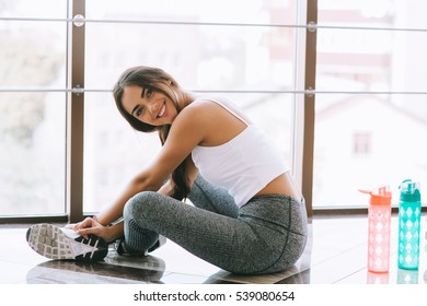 A young woman taking a break at the gym sitting on a pilates ball with a bottle of water or energy drink