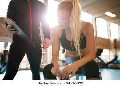 Young woman taking a break from her workout and looking at her fitness plan on clipboard. Female with her personal trainer at gym.