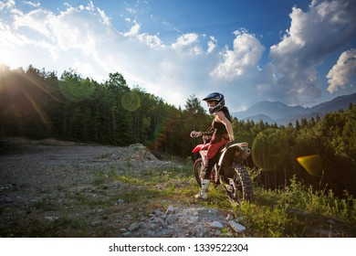 Young woman taking a break from riding motocross motorcyle in the woods