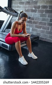 Young woman taking a break and using phone during her workout at the gym