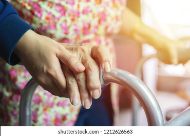 Young woman is taking care of the elderly woman while walking with a walker. Medical and healthcare concept.