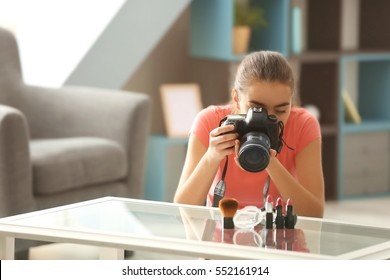 Young woman taking closeup pictures of makeup kit