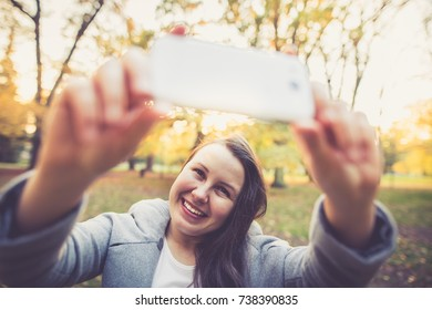 Young woman taking crazy selfie / photo by white smartphone in the park during lovely autumn (color toned image)