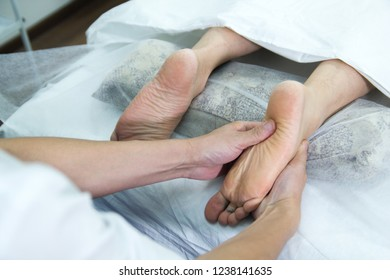 Young woman taking feet massage treatment in the clinic.