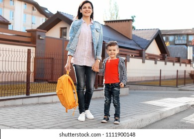 Young woman taking her little child to school