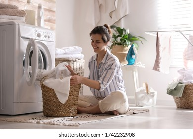 Young woman taking laundry out of washing machine at home