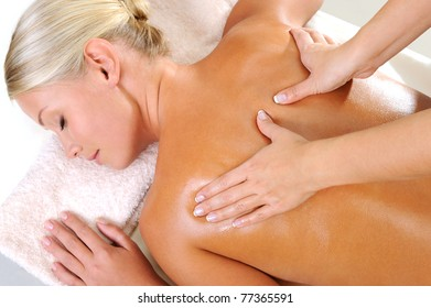 Young woman taking a massage for her body in beauty salon