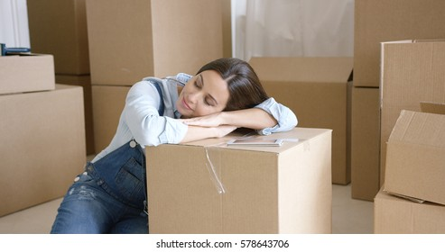 Young woman taking a nap on a brown carton