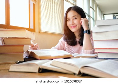 Young woman taking note and studying in library