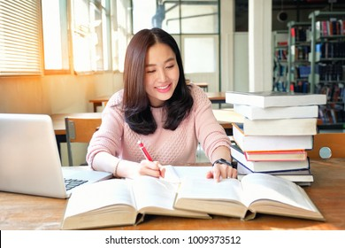 Young woman taking note and using laptop while studying in library