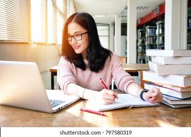 Junge Frau, die während des Bibliotheksstudiums mit Laptop mitnimmt und mit Laptop arbeitet
