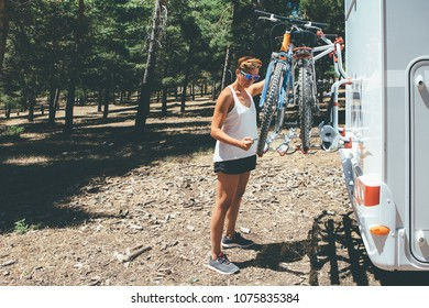 Young woman is taking off a bicycle from the caravan support placed at the back of the recreational vehicle on a holiday adventure trip. Copy space area available