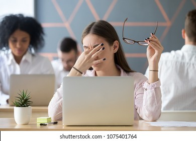 Young woman taking off glasses tired of computer work, exhausted student or employee suffering from eye strain tension or computer blurry vision problem after long laptop use, eyes fatigue concept - Shutterstock ID 1075401764