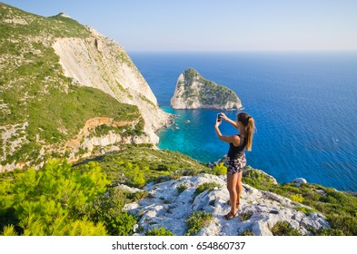 Young woman taking photo of cliff - Zakynthos island, Agalas, Greece