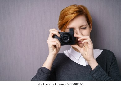 Young woman taking a photo with a compact camera holding it to her eye as she composes and focuses the shot