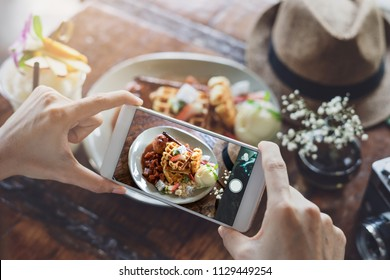 Young woman taking photo of food with smart phone in restaurant while travel
