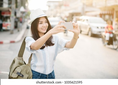 Young woman taking a photo with her phone,traveler concept