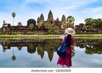 Young woman taking a photo with her phone at Angkor Wat in Cambodia