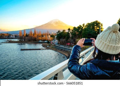 Young Woman taking photo with her phone of the view Mt.Fuji with Beautiful sunset at Lake Kawaguchiko in winter , Japan