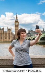 Young woman taking a photo of herself in front of the Westminster. London, England
