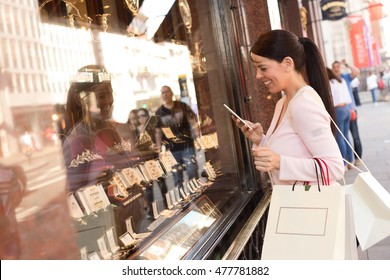 young woman taking a photo of a product in a shop window