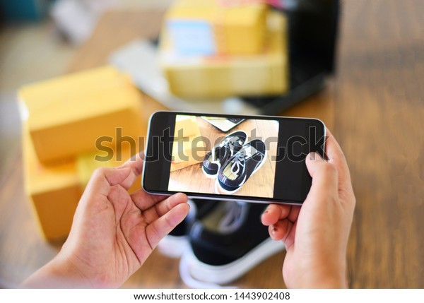 young woman taking photo sneakers with camera smartphone for post to sell online on the internet market website / selling online ecommerce shipping online shopping delivery and order concept
