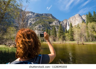 Young woman is taking a photo of Yosemite falls from Yosemite valley near Merced river in Yosemite National Park, United States of America