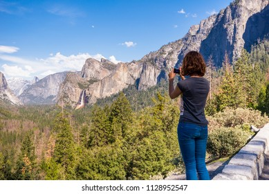 Young woman is taking a photo of Yosemite valley from Tunnel View in Yosemite National park, United states of America