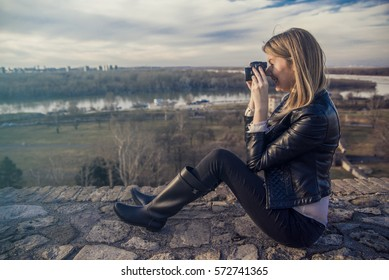 Young woman taking photograph of panoramic view. smiling young woman using a camera to take photo outdoors. Cute girl taking a picture using SLR camera