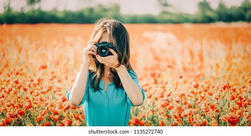 Young woman taking photographs with camera in poppies flower meadow in summer outdoor.
