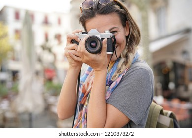 Young woman taking photographs on SLR