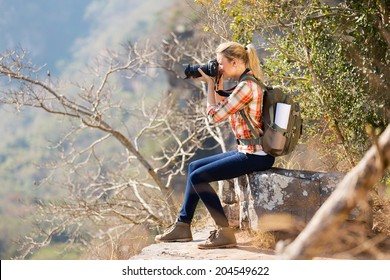 young woman taking photos by the edge of cliff