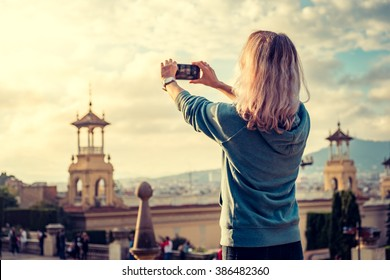 Young woman taking a picture of a city