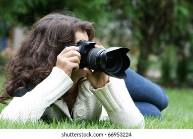 young woman taking picture on natural background