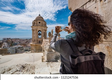 Young woman taking picture of the roofs of Cadiz, Spain.