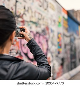 Young woman taking picture with smartphone of Berlin Wall.